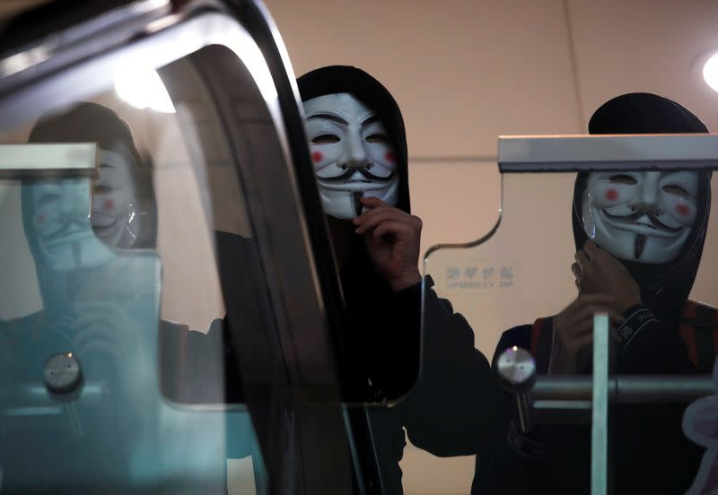 Anti government protesters wearing Guy Fawkes masks march inside the Sheung Shui shopping mall in Hong Kong
