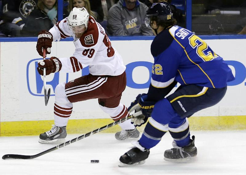 Phoenix Coyotes' Mikkel Boedker, left, of Denmark, passes the puck past St. Louis Blues' Kevin Shattenkirk during the first period of an NHL hockey game Tuesday, Nov. 12, 2013, in St. Louis. (AP Photo/Jeff Roberson)