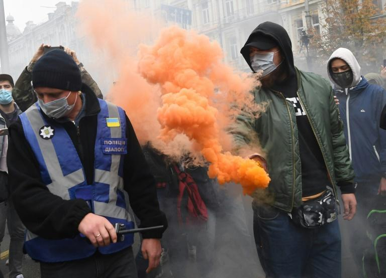 A demonstrator throws a smoke bomb during the protest outside the constitutional court building in Kiev on Friday