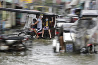 Residents wearing masks to prevent the spread of the coronavirus ride motorcycles as they negotiate a flooded road due to Typhoon Molave in Pampanga province, northern Philippines on Monday, Oct. 26, 2020. A fast moving typhoon has forced thousands of villagers to flee to safety in provinces. (AP Photo/Aaron Favila)