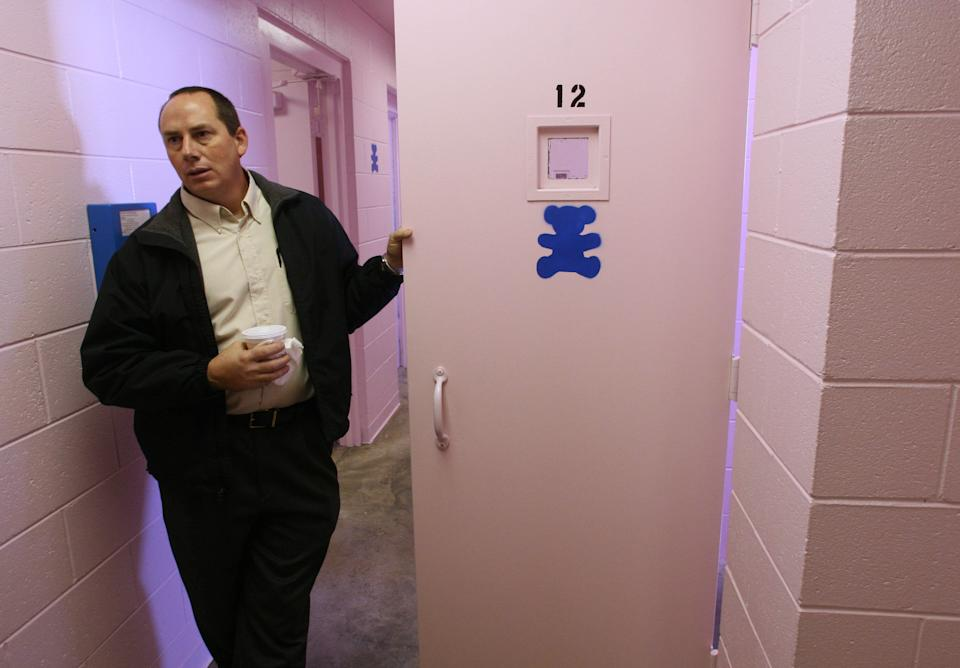 Dallas County sheriff Mike Rackley holds a pink cell door painted with a stencil of a teddy bear while talking about his jail's new color scheme, Thursday, November 2, 2006, in Buffalo, Mo. Rackley decided to turn things pink after vandalism and a small riot by inmates forced him to make repairs at the facility. (Photo by Mark Schiefelbein/WireImage)