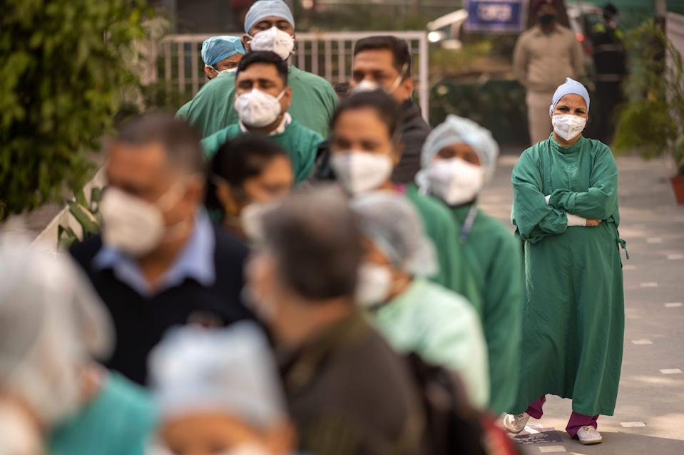 Medical workers wait to be inoculated with a Covid-19 coronavirus vaccine at a hospital in New Delhi on January 16, 2021. (Photo by Jewel SAMAD / AFP) (Photo by JEWEL SAMAD/AFP via Getty Images)