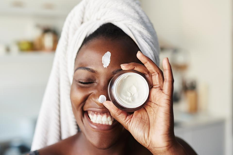 Shot of a beautiful young woman holding up a face cream product