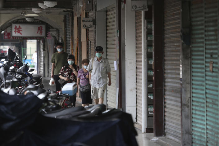 People wear face masks to help protect against the spread of the coronavirus walk past a row of closed shops after the COVID-19 alert rose to level 3 in Taipei, Taiwan, Tuesday, May 18, 2021. (AP Photo/Chiang Ying-ying)