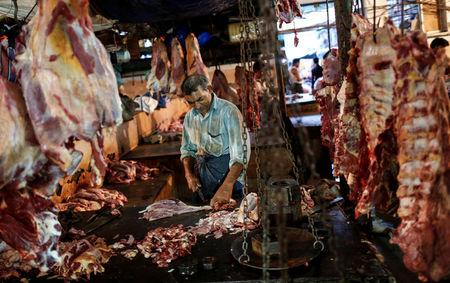 FILE PHOTO: A butcher cuts up portions of beef for sale in an abattoir at a wholesale market in Mumbai