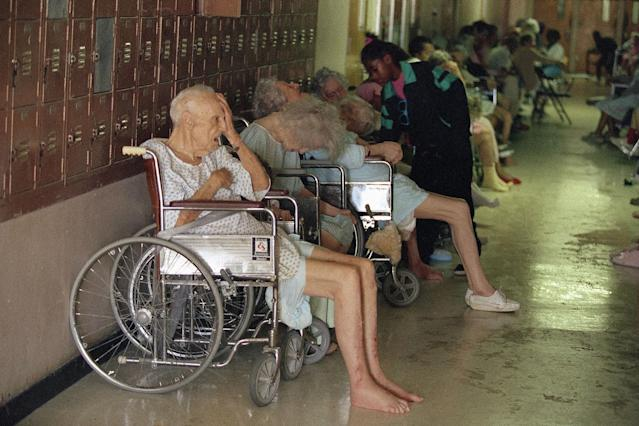 <p>Residents of a Homestead, Fla. nursing home line the halls of the Richmond Heights Middle School, Tuesday, Aug. 25, 1992, in Homestead, Fla. About 70 elderly residents were evacuated Monday, many lacking medicine. Officials said their former residence was wrecked by Hurricane Andrew. (AP Photo/Chris O'Meara) </p>