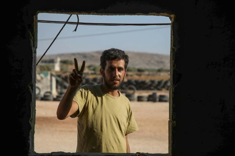 Mohammad al-Naeemi, a Syrian who returned from exile in Germany to join a rebel group, flashes a victory sign at a training camp near the Bab al-Hawa crossing between Iblib province and Turkey on July 18, 2019 (AFP Photo/Aaref WATAD)