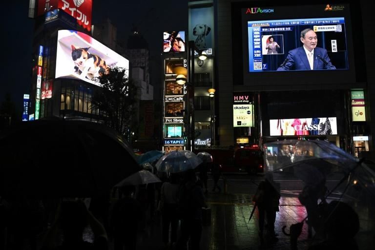 A large screen in Tokyo shows a live broadcast of Japan's Prime Minister Yoshihide Suga announcing a new virus state of emergency stretching throughout the Olympics
