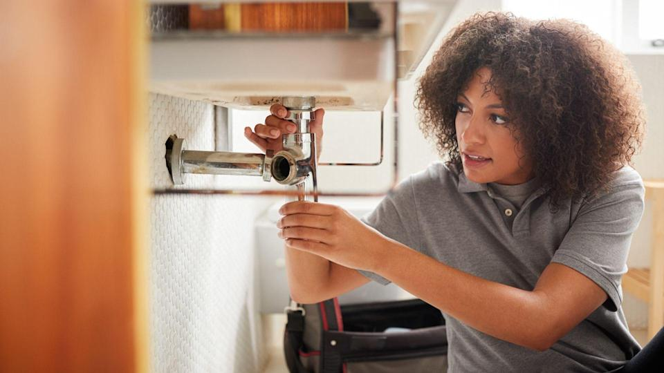 Young black female plumber sitting on the floor fixing a bathroom sink, seen from doorway.