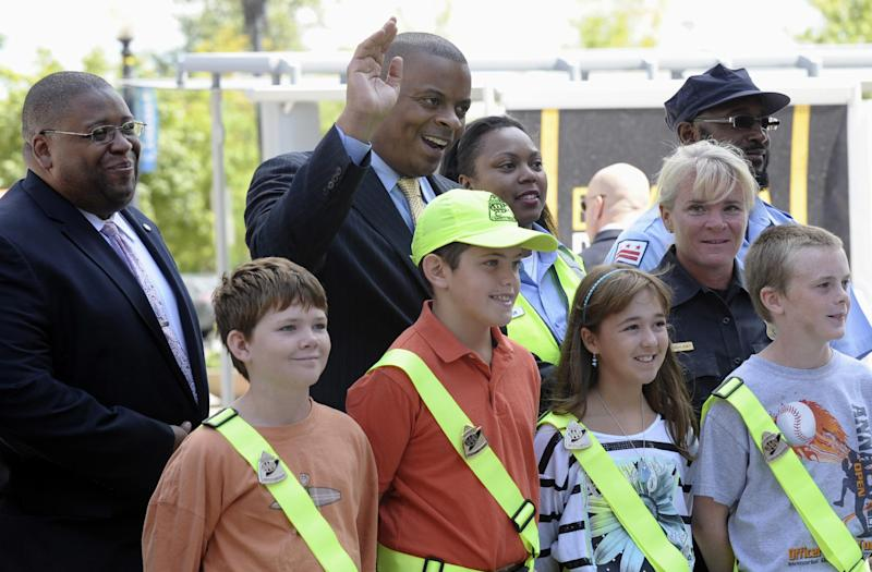 Transportation Secretary Anthony Foxx, center, and National Highway Traffic Safety Administration Administrator (NHTSA) David Strickland, left. stand with students wearing crossing guard belts during a news conference outside the Transportation Department in Washington, Monday, Aug. 5, 2013. Secretary Foxx announced a new set of tools to help communities combat the rising number of pedestrian deaths that have occurred over the last two years. (AP Photo/Susan Walsh)