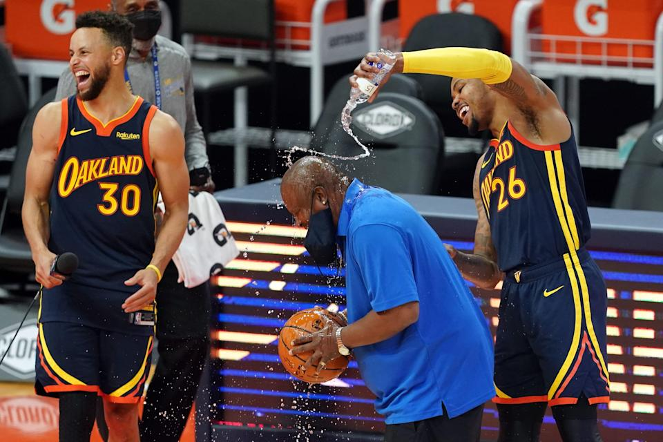 Golden State Warriors forward Kent Bazemore (26) pours water on guest public address announcer Aaron Taylor as guard Stephen Curry (30) laughs after the game against the Houston Rockets at Chase Center.