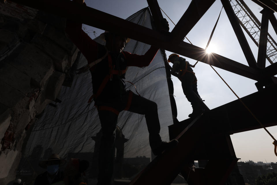 Workers climb on a metal frame beside the damaged cupola, in the early stages of reconstruction work at Nuestra Senora de Los Angeles, or Our Lady of Angels church, three years after an earthquake collapsed nearly half of its 18th-century dome in Mexico City, Wednesday, Sept. 23, 2020. About half of the 2,340 colonial-era buildings and churches damaged in the 2017 Mexico quake still need to be repaired, restored or partially rebuilt. (AP Photo/Rebecca Blackwell)