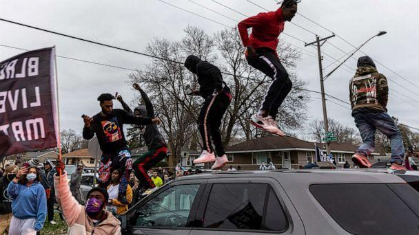 PHOTO: Protesters stand on top of a car as they clash with police after an officer shot and killed a driver during a traffic stop in Brooklyn Center, Minnesota, on April 11, 2021. (Kerem Yucel/AFP via Getty Images)