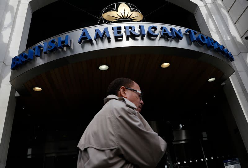 A man walks past the British American Tobacco offices in London
