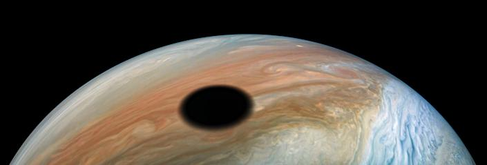 jupiter moon io casts shadow over the colorful bands of the planet