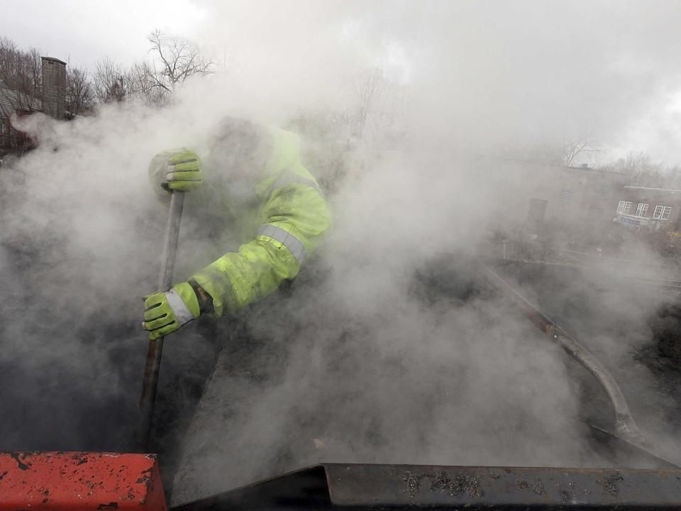Billy Rennei prepares some asphalt at the city yards in Pittsfield, Mass., for an emergency road repair on Jason Street before the plows hit the streets before a looming snow storm. Wednesday, Dec. 16, 2020. (Ben Garver/The Berkshire Eagle via AP)