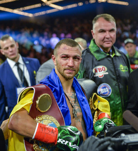 Vasiliy Lomachenko poses with the belts after defeating Jose Pedraza in the WBO title lightweight boxing match at Madison Square Garden, Saturday, Dec. 8, 2018, in New York. (AP Photo/Howard Simmons)