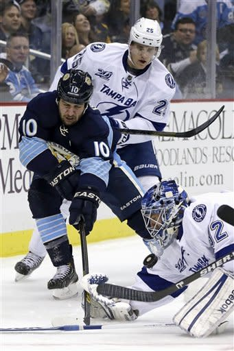 Pittsburgh Penguins center Tanner Glass (10) battles for a rebound with Tampa Bay Lightning goalie Anders Lindback (39) and Tampa Bay Lightning defenseman Matt Carle (25) in the second period of an NHL hockey game in Pittsburgh Sunday, Feb. 24, 2013. (AP Photo/Gene J. Puskar)