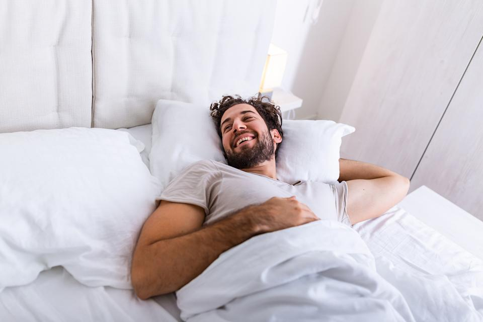 Young man sleeping waking up and stretching in his bed. people, bedtime and rest concept - man lying in bed at home, It's time to wake up