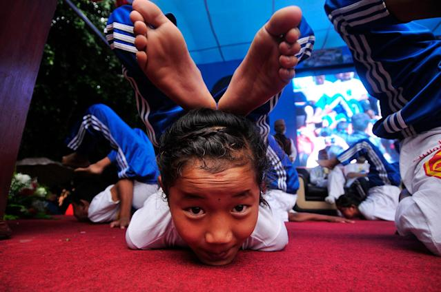 <p>Children from Patanjali Yogpeeth Ashram, a trust run by Indian yog guru Ramdev performing Yoga Position as a part of International Day of Yoga celebration at Kathmandu, Nepal on Wednesday, June 21, 2017. (Photo: Narayan Maharjan/NurPhoto via Getty Images) </p>
