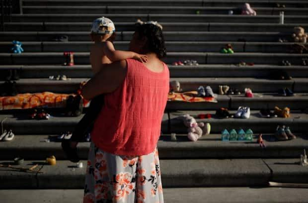 Regina Haasjes and her grandson Marcus, 3, of the Tla-O-Qui-Aht First Nation, pay their respects below the steps outside the legislature in Victoria, B.C., on June 1. (Chad Hipolito/Canadian Press - image credit)