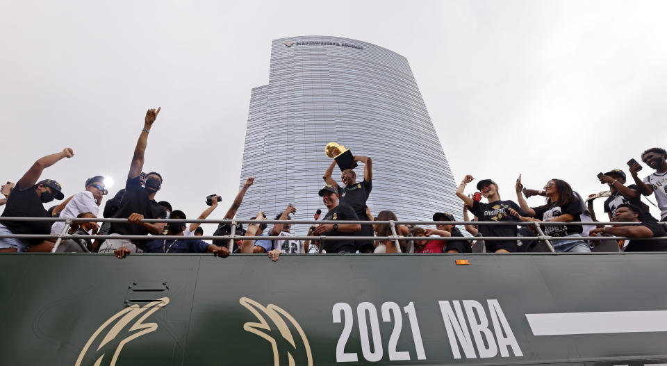 Milwaukee Bucks' Giannis Antetokounmpo, third from left, gestures during a parade for the basketball team's NBA Championship win, Thursday, July 22, 2021, in Milwaukee. (AP Photo/Jeffrey Phelps)
