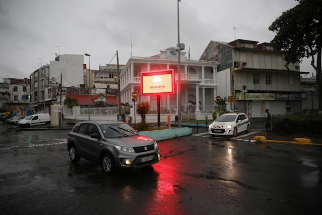 """<p>A car passes next to a banner warning of a """"Red Alert"""" for rains as Hurricane Maria approaches in Pointe-a-Pitre, Guadeloupe island, France, Sept. 18, 2017. (Photo: Andres Martinez Casares/Reuters) </p>"""
