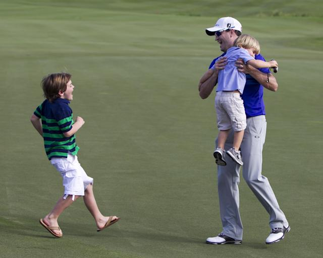 Zach Johnson, picks up his son Wyatt, 3, as son Will, 7, runs out to greet him after Johnson won the final round of the Tournament of Champions golf tournament, Monday, Jan. 6, 2014, in Kapalua, Hawaii. (AP Photo/Marco Garcia)