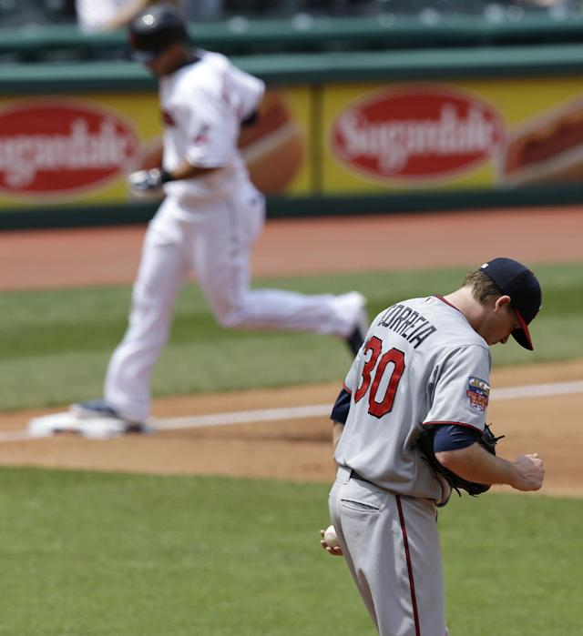 Minnesota Twins starting pitcher Kevin Correia, bottom, waits for Cleveland Indians' Michael Brantley to run the bases after Brantley hit a two-run home run in the fifth inning of a baseball game, Thursday, May 8, 2014, in Cleveland. The Indians won 9-4. (AP Photo/Tony Dejak)