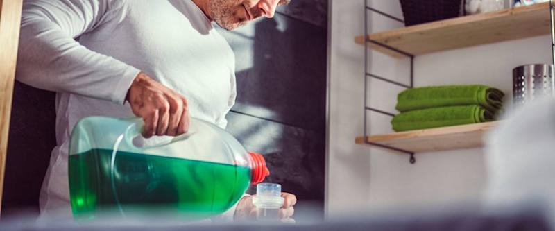 Man wearing white shirt pouring liquid laundry detergent In the bottle cap at laundry room