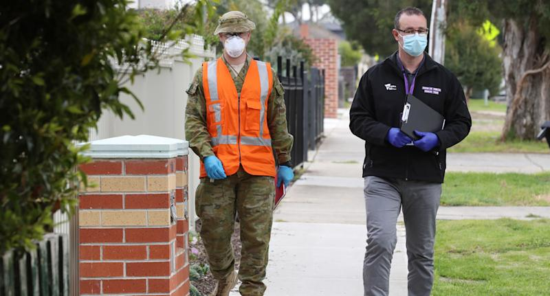An ADF member and health worker on a street in Melbourne, which is under Stage 4 restrictions.