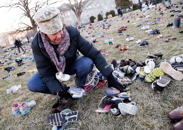 <p>A volunteer lays out 7,000 empty pairs of shoes for every child killed by guns in the US since Sandy Hook at the U.S. Capitol Building on Tuesday, March 13, 2018 in Washington. (Photo: Paul Morigi/AP Images for AVAAZ) </p>
