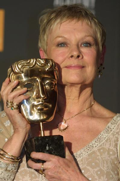 """FILE - In this Feb. 24, 2002 file photo, British actress Dame Judi Dench poses with her 2002 British Academy of Film and Television Arts (BAFTA) award for best actress in a leading role for her portrayal of novelist Iris Murdoch in the film """"Iris,"""" at the award ceremony in London. (AP Photo/Alastair Grant, File)"""