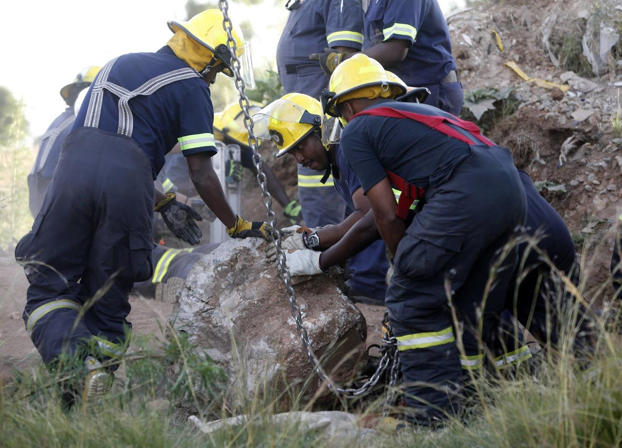 Rescue officials move a rock removed from an abandoned gold shaft as they work to rescue trapped suspected illegal miners in Benoni, east of Johannesburg, February 16, 2014. South African rescuers started bringing to the surface at least 30 illegal miners on Sunday who had been trapped by debris in the abandoned gold shaft near Johannesburg, emergency services ER24 spokesman Werner Vermaak said. There were no immediate reports of deaths or injuries. Vermaak later told Reuters that some of the miners still underground were refusing to come up, saying they did not want to be arrested. REUTERS/Mike Hutchings (SOUTH AFRICA - Tags: BUSINESS COMMODITIES CRIME LAW DISASTER)