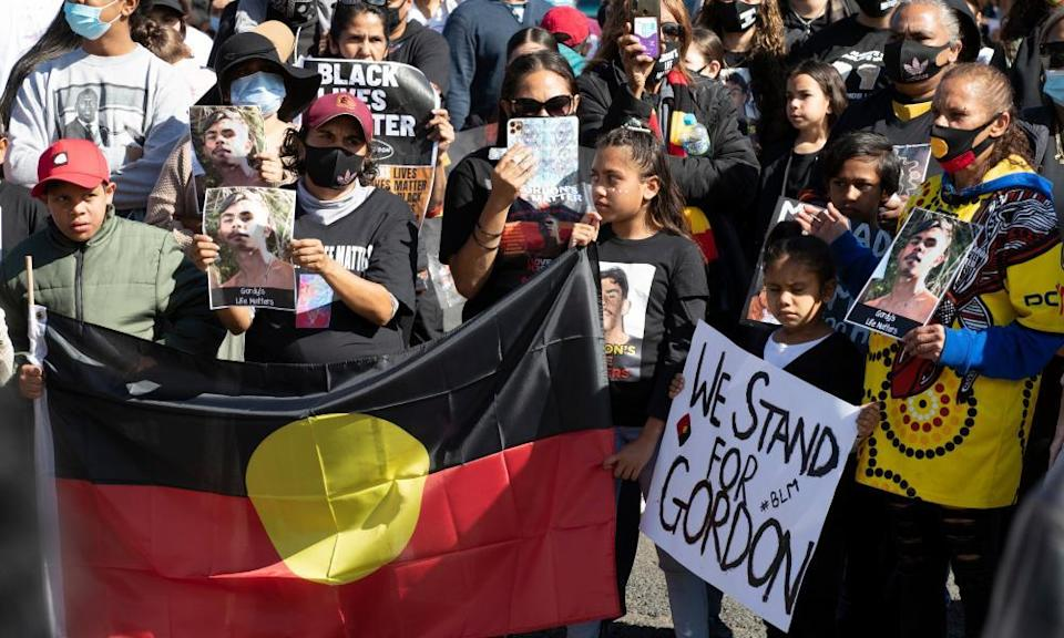 Demonstrators with an Aboriginal flag and signs at the rally