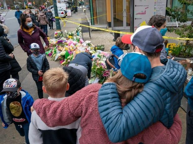 A family embraces at a makeshift memorial outside the Lynn Valley public library. The quiet suburb of the city's North Shore is a haven for young families and retired couples.