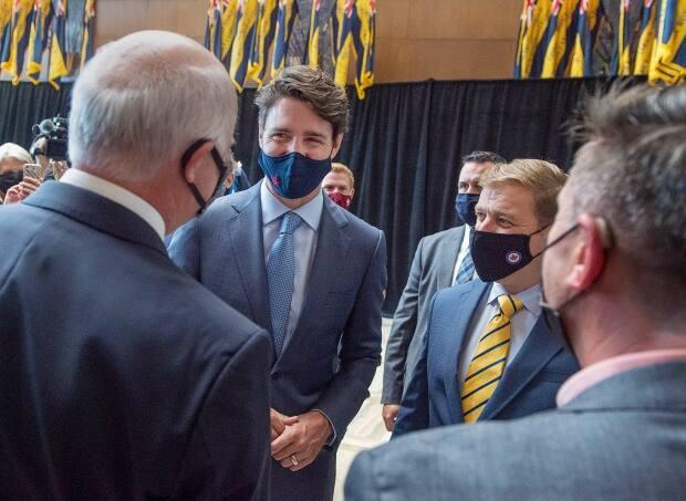 Liberal Leader Justin Trudeau, left, and Newfoundland and Labrador Premier Andrew Furey are greeted as they walk from the Confederation Building in St. John's last month.  (The Canadian Press/Andrew Vaughan - image credit)