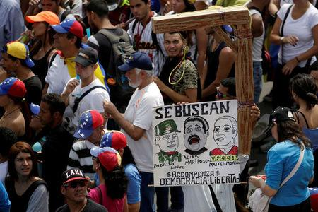 "Opposition supporters carry a placard depicting (L-R) Venezuela's Defense Minister Vladimir Padrino Lopez, Venezuela's President Nicolas Maduro and Venezuela's Supreme Court President Maikel Moreno that reads ""Wanted"" during a rally in Caracas, Venezuela April 24, 2017. REUTERS/Marco Bello"