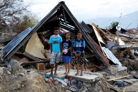 Muhammad Nur, 27, his wife Nita Puspita, 25 and Nita's sister Widya Wijayanti, 14, stand in front of their former home, obliterated by ground liquefaction looking for useful items, in Petobo neighbourhood, Palu, Central Sulawesi, Indonesia, October 11, 2018.  REUTERS/Jorge Silva