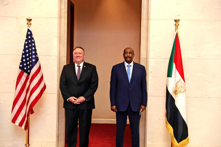 FILE - In this Aug. 25, 2020 file photo, U.S. Secretary of State Mike Pompeo stands with Sudanese Gen. Abdel-Fattah Burhan, the head of the ruling sovereign council, in Khartoum, Sudan. The U.S. Embassy in Khartoum said the administration removed Sudan from the U.S. list of state sponsors of terrorism, a move that could help the African country get international loans to revive its battered economy and end its pariah status. The embassy said in a Facebook post that the removal of Sudan from the list is effective as of Monday, Dec. 14, 2020. Delisting Sudan from the state sponsors blacklist is a key incentive for the Sudanese government to normalize relations with Israel. (Sudanese Cabinet via AP, File)