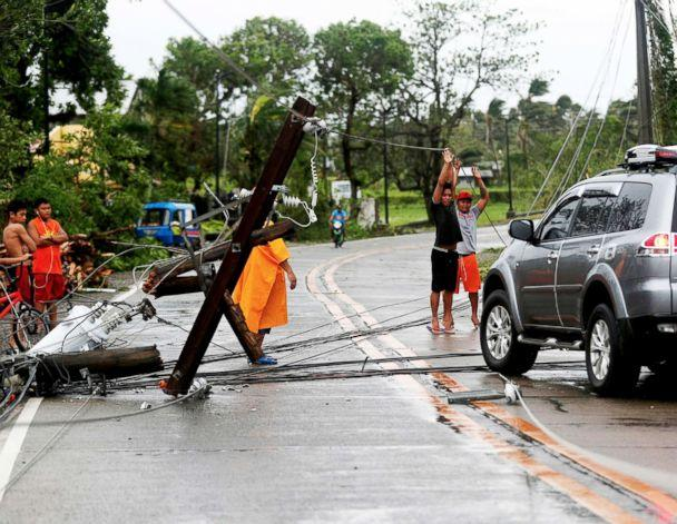 PHOTO: Filipino villagers lift electric wires in the typhoon-hit town of Lal-lo, Cagayan province, Philippines, Sept. 15, 2018. (Francis R. Malasig/EPA via Shutterstock)
