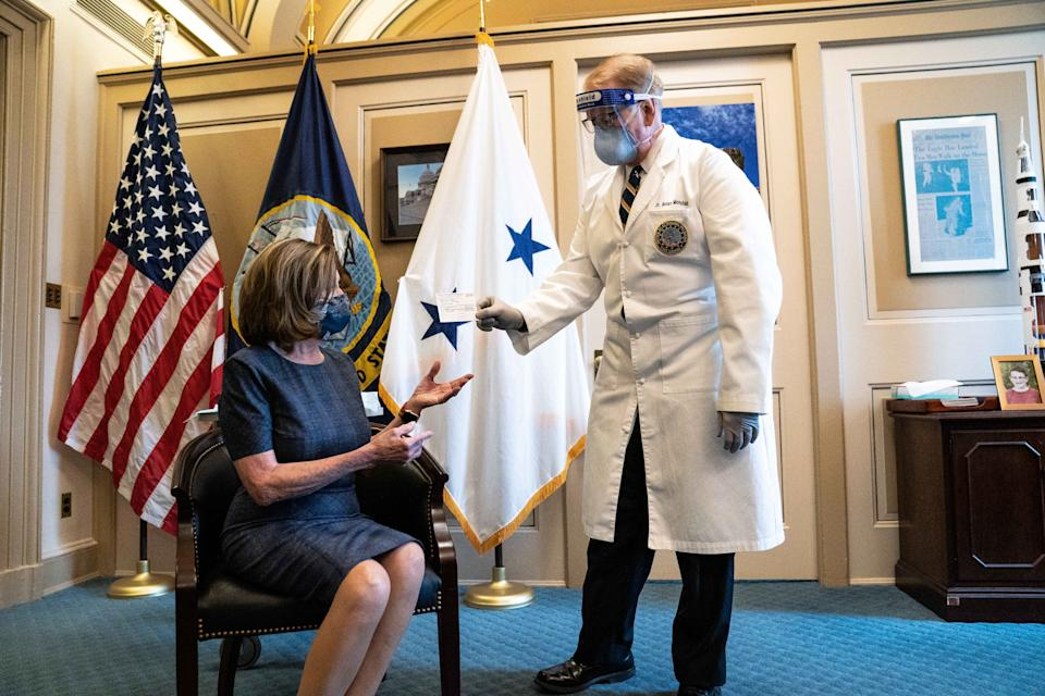 WASHINGTON, DC - DECEMBER 18: Brian Monahan, the Attending Physician of the United States Congress, gives a medical card to House Speaker Nancy Pelosi (D-CA) in the U.S. Capitol Building on December 18, 2020 in Washington, DC. (Photo by Anna Moneymaker-Pool/Getty Images)