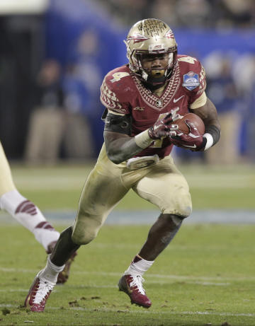 FILE - In this Saturday, Dec. 6, 2014 file photo, Florida State's Dalvin Cook (4) runs against Georgia Tech during the second half of the Atlantic Coast Conference championship NCAA college football game in Charlotte, N.C. Florida State is suspending running back Dalvin Cook indefinitely after a woman accused him of punching her outside a downtown bar. The school announced the decision Friday, July 10, 2015 after the state attorney issued a warrant for Cook's arrest on a misdemeanor battery charge. (AP Photo/Chuck Burton, File