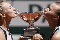 Czech Republic's Barbora Krejcikova, right, and compatriot Katerina Siniakova kiss the cup after defeating USA's Bethanie Mattek-Sands and Poland's Iga Swiatek in their women's doubles final match of the French Open tennis tournament at the Roland Garros stadium Sunday, June 13, 2021 in Paris. (AP Photo/Thibault Camus)
