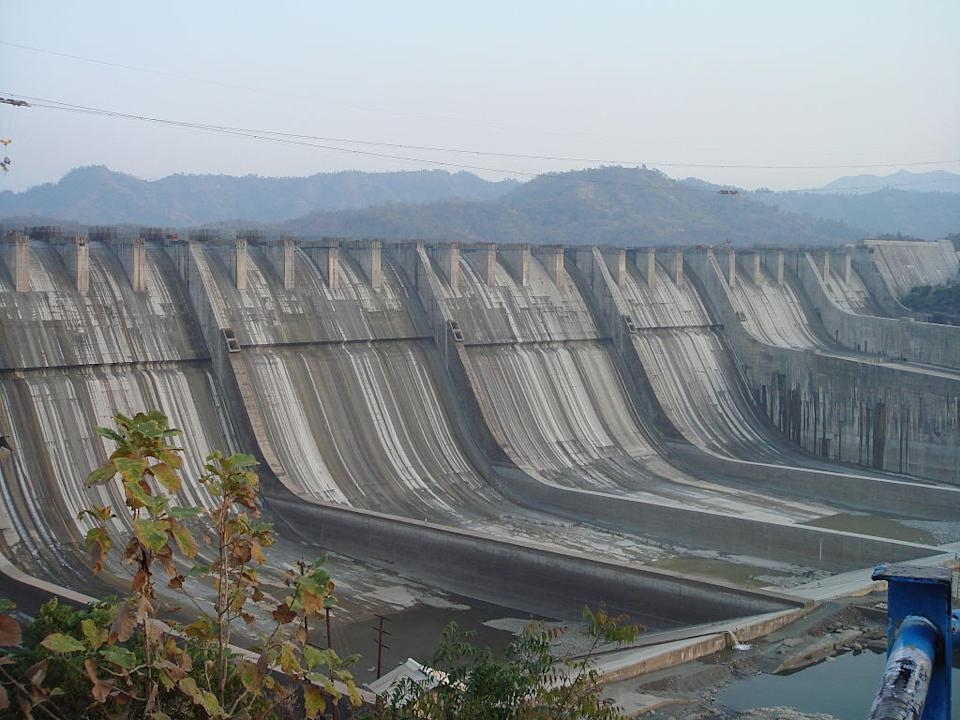 The Sardar Sarovar Dam is a gravity dam on the Narmada River near Navagam, Gujarat, India. It is the largest dam and part of the Narmada Valley Project, a large hydraulic engineering project involving the construction of a series of large irrigation and hydroelectric multi-purpose dams on the Narmada River. The project took form in 1979 as part of a development scheme to increase irrigation and produce hydroelectricity. It is the 30th largest dams planned on river Narmada, Sardar Sarovar Dam (SSD) is the largest structure to be built. It has a proposed final height of 163 m (535 ft) from foundation. The dam is one of India's most controversial dam projects and its environmental impact and net costs and benefits are widely debated. The World Bank was initially a funder of the SSD, but withdrew in 1994. The Narmada Dam has been the centre of controversy and protest since the late 1980s. [Photo by AceFighter19 (Own work) [Public domain], via Wikimedia Commons]