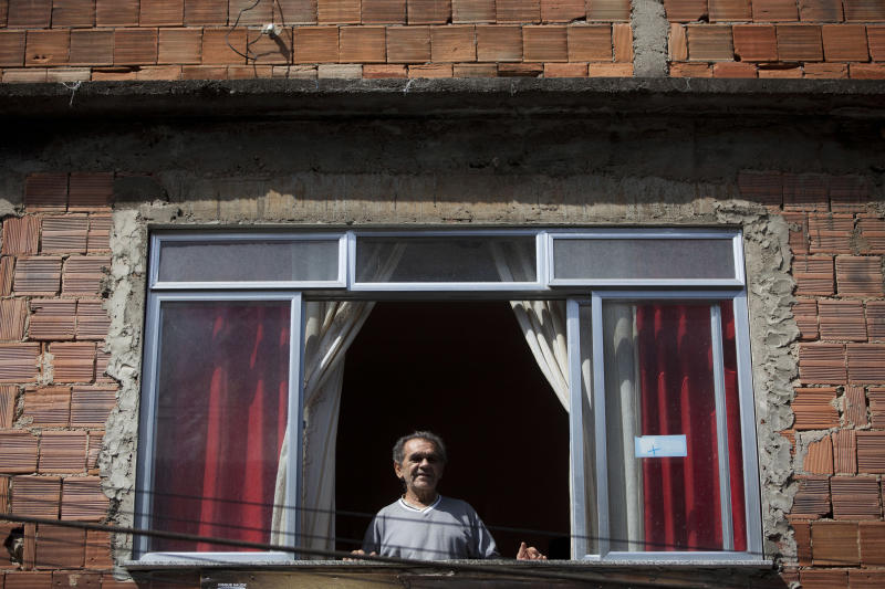 In this May 10, 2012 photo, Jose Nazare Braga looks out from his home in the Rocinha shantytown in Rio de Janeiro, Brazil. The building is Braga's nest egg, his retirement home and an inheritance for his large family. But for decades, the property wasn't formally his, and he lived in far he might lose it all. Now local officials and human rights groups are working to give legal title to tens of thousands of people like Braga, a process that increases their wealth and gives them greater access to credit, as well as peace of mind. (AP Photo/Felipe Dana)