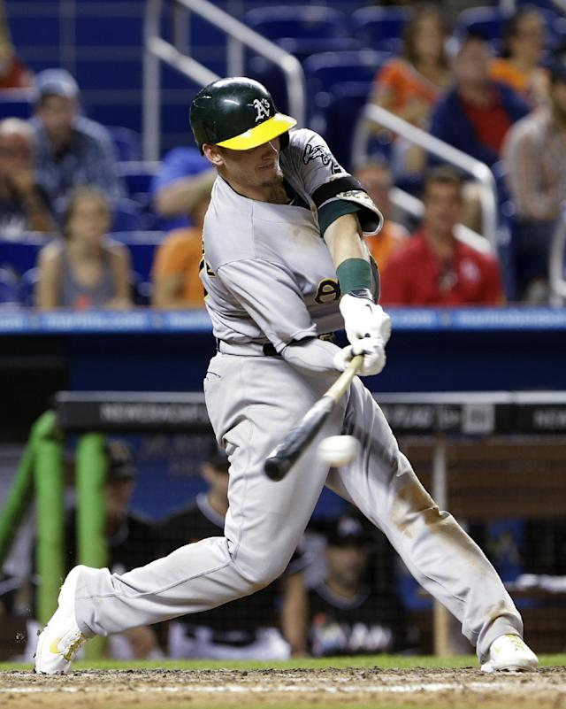 Oakland Athletics' Josh Donaldson hits a two-out RBI single to score Brandon Moss for the go-ahead run during the 14th inning of a baseball game against the Miami Marlins, Saturday, June 28, 2014 in Miami. The Athletics won 7-6 in 14 innings. (AP Photo/Wilfredo Lee)