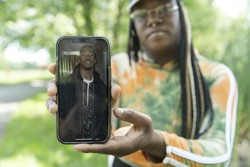 Jalisa Martin shows a photo of her brother, 18-year-old Winfred Jackson Jr., who was found shot dead in 2020.