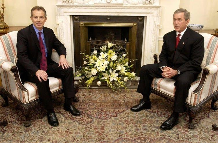 A 2003 photo of Tony Blair and George W Bush sitting in armchairs in front of a fireplace during a meeting at Downing Street.