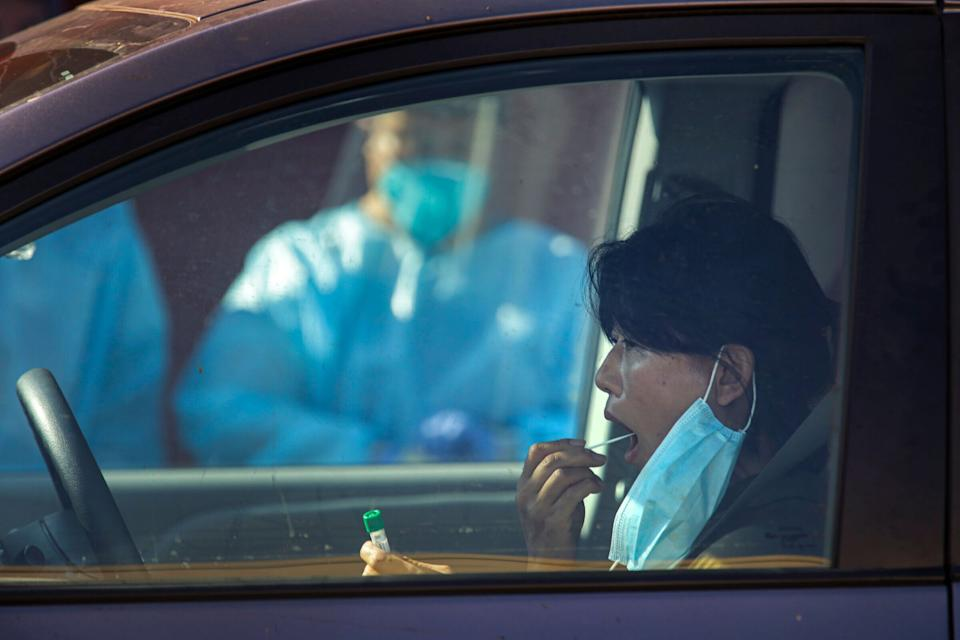 LOS ANGELES, CA - OCTOBER 03: A lady uses oral swab for COVID-19 test at a free drive-thru test site organized by Councilman Herb Wesson in collaboration with Kheir Clinic at his district office on Saturday, Oct. 3, 2020 in Los Angeles, CA. (Irfan Khan / Los Angeles Times via Getty Images) (Photo: Irfan Khan via Getty Images)